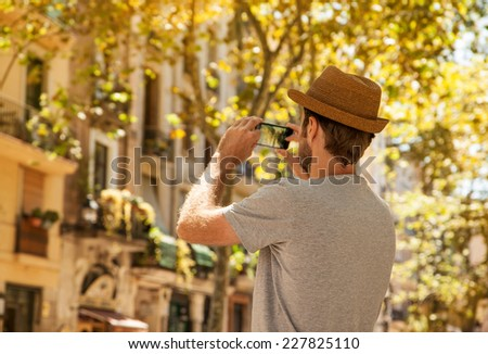 Caucasian tourist man takes photo on mobile phone outdoor among old city buildings - summer holiday traveling - stock photo
