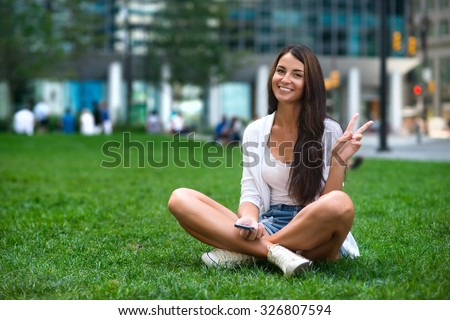 Caucasian tourist young beautiful woman sitting on the green grass at city park and showing victory v hand sign - stock photo