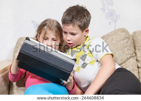 Caucasian two children having fun with tablet pc while sitting on couch - stock photo