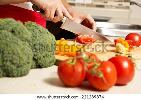 caucasian woman about to cut raw vegetables  on the kitchen