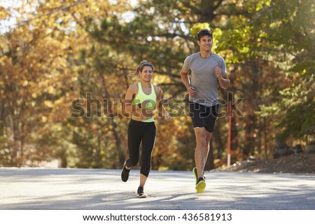 Caucasian woman and man jogging on a country road