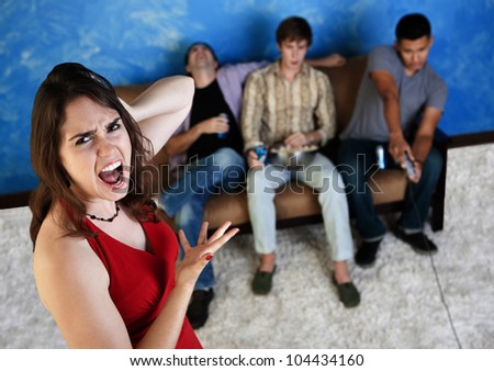 Caucasian woman annoyed with three men playing video games