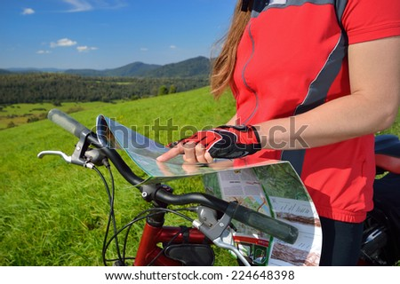 Caucasian woman cyclist with map in the summer mountains. Outdoor activity. Bieszczady Poland. - stock photo