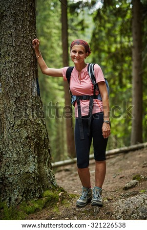 Caucasian woman hiker leaning against a tree in a pine forest - stock photo