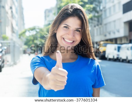 Caucasian woman in a blue shirt in the city showing thumb up - stock photo