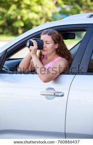 Caucasian woman in vehicle with camera in hands shooting some attractions