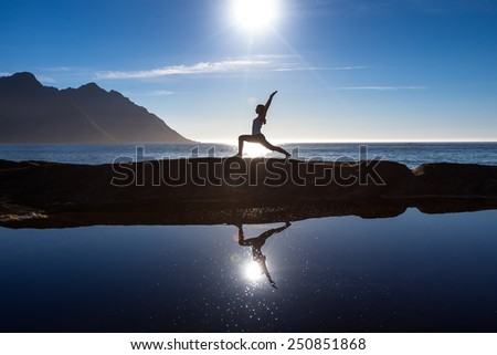 Caucasian woman is doing yoga excercises against picturesque landscapes in Norway - stock photo