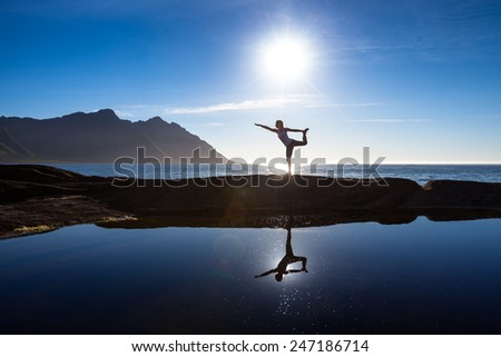 Caucasian woman is doing yoga exercises against picturesque landscapes in Norway - stock photo