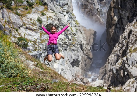 Caucasian woman is jumping in mountanis in front of big waterfall - stock photo