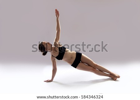 Caucasian woman is practicing yoga . In studio.  grey background.