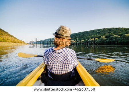 Caucasian woman is relaxing in kayak on the river. Ukraine.