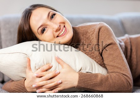 Caucasian woman is smiling towards the camera while hugging a pillow - stock photo