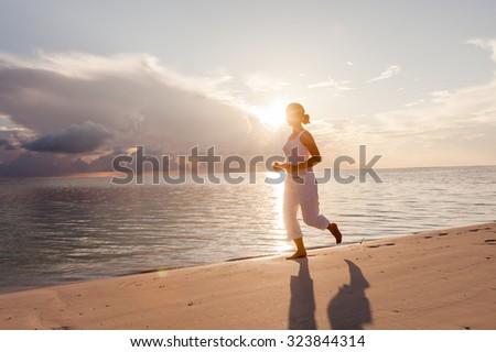 Caucasian woman jogging at the seashore - stock photo