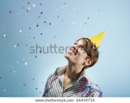 caucasian woman looking at confetti in the air. Horizontal shape, side view, head and shoulders, copy space