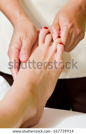 caucasian woman on a tropical vacation receiving a foot massage