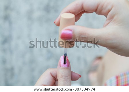 Caucasian woman painting nails color pink - stock photo