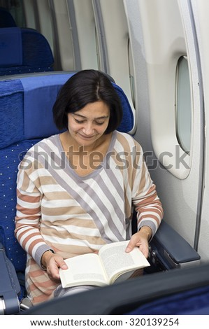 caucasian woman passenger in airplane reading a book on the seat - stock photo