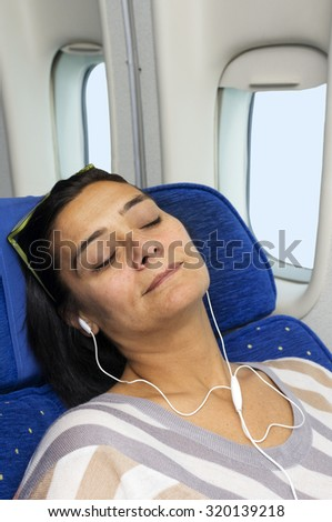 caucasian woman passenger in airplane  resting on the seat  using mobile smart device with  headphones  in comfortable flight and trip - stock photo