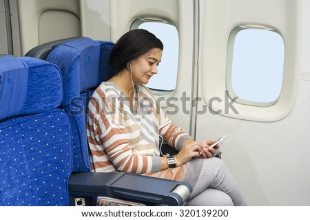 caucasian woman passenger in airplane using mobile  smart device  with headphones  in comfortable flight and trip - stock photo