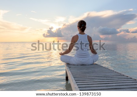 Caucasian woman practicing yoga at seashore - stock photo