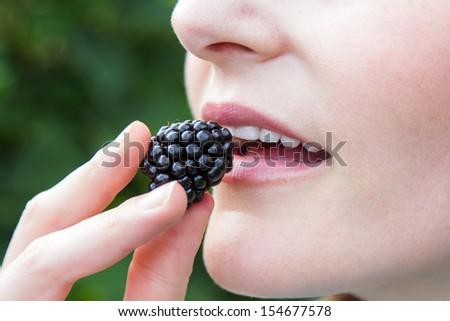 Caucasian woman putting blackberry into mouth closeup - stock photo