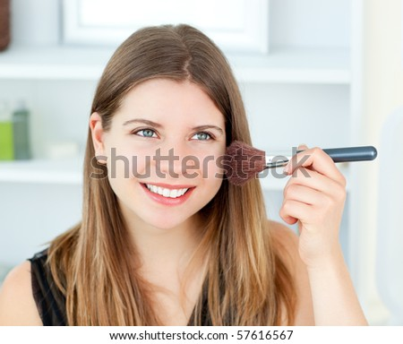 Caucasian woman putting make-up on her face