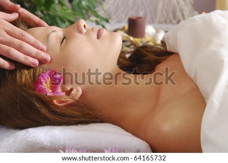 Caucasian woman receiving facial massage at spa. - stock photo