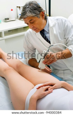caucasian woman receiving laser treatment at the leg from a male doctor - stock photo
