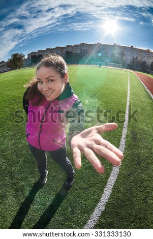Caucasian woman showing opened palm while standing green grass of playing field in stadium - stock photo
