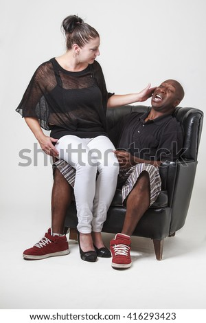 caucasian woman sitting on a black man lap and slapping him on the face