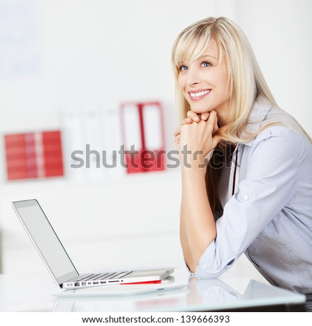 Caucasian woman sitting while daydreaming in front of her laptop