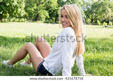 Caucasian woman smiling happy on sunny summer or spring day outside in park. - stock photo