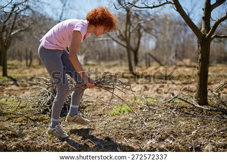Caucasian woman spring cleaning the orchard, gathering cut branches to throw them away