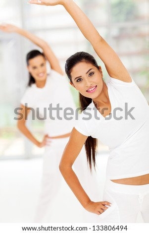 caucasian woman stretches her body for fitness with friend on background - stock photo