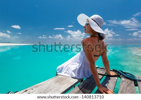 Caucasian woman takes rest at wooden pier to Indian ocean - stock photo