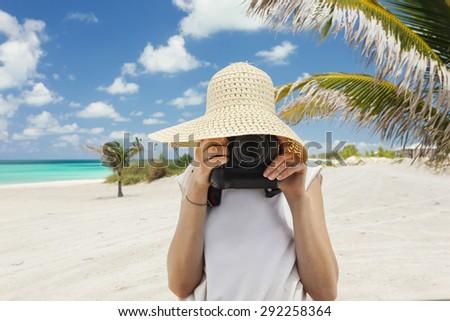 Caucasian woman taking photos on a tropical island - stock photo