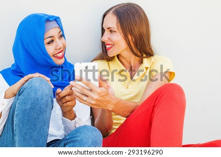 caucasian woman using phone together with asian muslim girl - stock photo