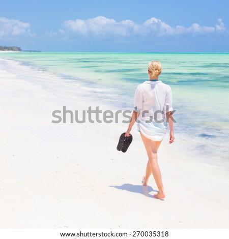 Caucasian woman walking joyfully on tropical beach. Beautiful caucasian model  wearing white beach tunic on vacations walking down picture perfect Paje beach, Zanzibar, Tanzania. Copy space. - stock photo
