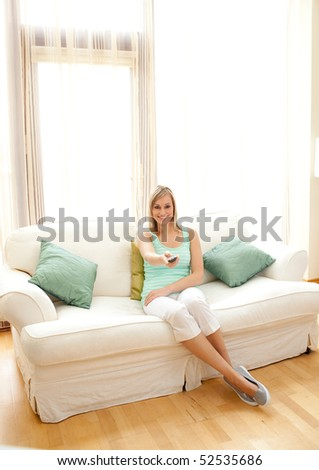Caucasian woman watching TV sitting on a sofa - stock photo