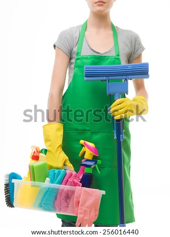 caucasian woman wearing apron and holding cleaning supplies and mop, on white background - stock photo