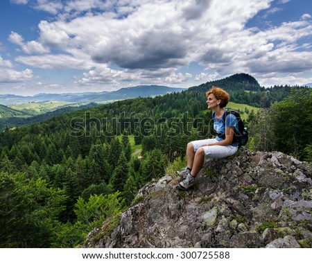 Caucasian woman with backpack sitting on a mountain top - stock photo