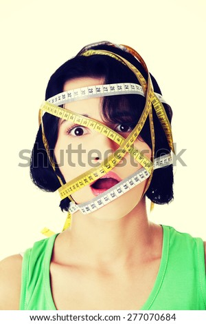 Caucasian woman with measuring tape on face. - stock photo