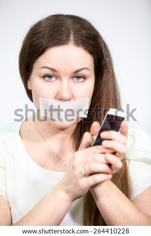 Caucasian woman with mouth sealed tape holding a cell phone in hands, grey background - stock photo