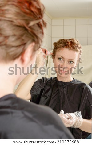 Caucasian woman with short hair dying her hair red in front of mirror in her own bathroom. - stock photo