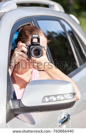 Caucasian woman with slr camera photographing from vehicle sitting inside