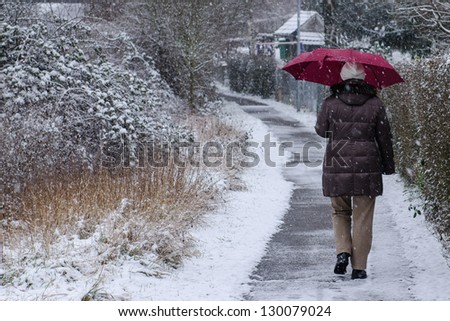 Caucasian woman with umbrella is strolling on a footpath - stock photo
