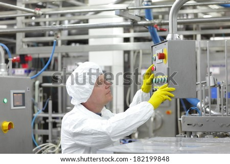 caucasian worker  at control panel panel in factory - pressing buttons  - stock photo