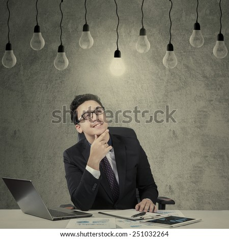 Caucasian worker in business suit working on desk while looking up at bright lightbulb - stock photo