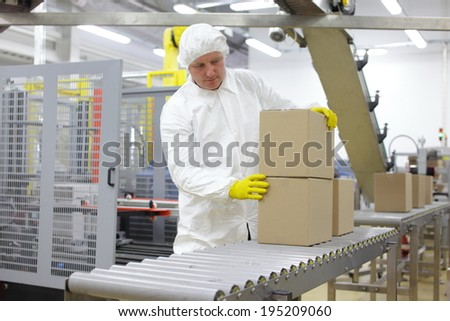caucasian worker in white apron at packing line in factory - stock photo