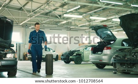 Caucasian young attractive auto mechanic man in blue uniform with blue gloves rolling wheel going on the autoservice. Indoor.